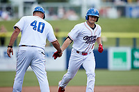 Chase Krogman (1) of the Kannapolis Cannon Ballers slaps hands with third base coach Guillermo Quiroz (40) after hitting  home run against the Carolina Mudcats at Atrium Health Ballpark on June 13, 2021 in Kannapolis, North Carolina. (Brian Westerholt/Four Seam Images)