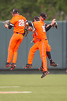 Oklahoma State Cowboys outfielders Corey Hassel #28, Aaron Cornell #19 and Conor Costello #24 celebrate after the NCAA baseball game against the Texas Longhorns on April 26, 2014 at UFCU Disch–Falk Field in Austin, Texas. The Cowboys defeated the Longhorns 2-1. (Andrew Woolley/Four Seam Images)