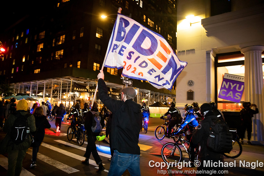 A demonstrator carries a Biden flag during a protest demanding every vote cast be counted in the 2020 presidential election between U.S. President Donald Trump and former Vice President Joe Biden on November 4, 2020 in New York City.  Photograph by Michael Nagle
