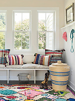 In one corner a bench seat with cushions is set beneath the window. A wicker Ali Baba basket stands on a colourful rag rug.