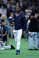SEATTLE, WA:  Ken Griffey Jr. stands on the field holding his daughter Taryn Griffey before a game against the Oakland Athletics at the Kingdome in Seattle, Washington in 1996. (Photo by Brad Mangin)