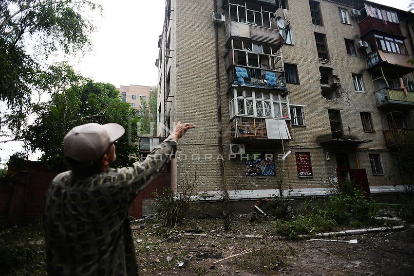 A civilian shows damaged houses by Ukraine shelling.  Slavyanks, Ukraine.