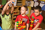 Preschool ages 3-5 three boys playing separately side by side with constructions made of plastic connecting Duplo bricks horizontal