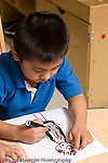 Education preschool 4 year olds art activity boy drawing recognizable shape with markers human figure vertical