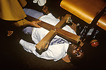 Mount Zion Spiritual Baptist church North London. A cross is placed across  a man who lies in a trance, as that evil spirits are exorcised from his body. 1990s