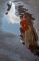 Reflection in a pool of water with the Vietnamese Flag and general and interesting street scenes in Ho Chi Minh City.<br /> Saigon or in Vietnamese Ho Chi Minh City street life where old and new architecture mix in harmony. The bustling Metropolis of South Vietnam.