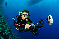Woman scuba diver holding a reflex camera inside a housing and using a strobe, and breathing on a regulator in the Red Sea, of Safaga coast, Egypt (MR)