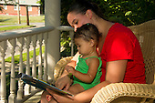 MR / Schenectady, NY. Mother (20) reads a book to her infant daughter (girl, 9 months, African American & Caucasian). MR: Dal4, Dal6. ID: AL-HD. © Ellen B. Senisi