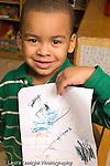 Education preschool proud boy holding up his drawing art activity vertical