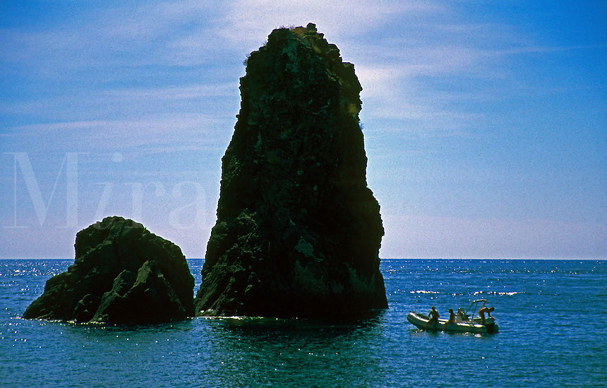 Three Italian bathers in a boat on the Mediterranean Sea in Aci Castello, Sicily, Italy.