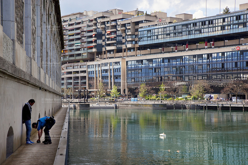 """Switzerland. Geneva. A police officer search the belongings of a convict man who got arrested while selling drugs in the streets. The prisoner is handcuffed and stands close to the """" Batiments des Forces Motrice s"""". Modern architecture and the Rhone river. Swan and ducks swimm in the water. The inmate is an arab man from the Maghreb area. A frisk search (also called a patdown or pat down) is a search of a person's outer clothing wherein a person runs his or her hands along the outer garments to detect any concealed weapons or contraband. 3.05.12 © 2012 Didier Ruef.."""