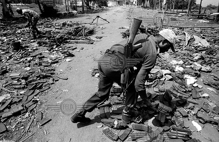 Congolese soldiers sorting through a pile of discarded weapons and ammunition clips on the border with Rwanda. The Hutu dominated regime in Rwanda had been defeated by the Rwandan Patriotic Front (RPF), and hundreds of thousands of Hutus, including the perpetrators of the genocide and the defeated army, had flooded into DR Congo (then known as Zaire). The Congolese authorities instructed the former Rwandan army to leave their weapons behind.