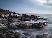 Waves break softly on the shore of the Beavertail Lighthouse.
