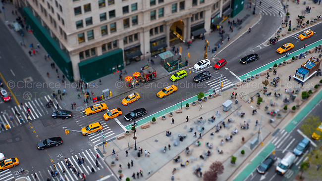 Traffic and pedestrians move through Madison Square at the intersection of 5th Avenue and 23rd / 24th streets in New York City in a tilt-shift miniature effect view.