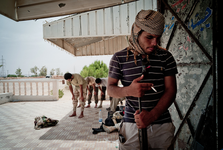 Rebel fighters pray at the crossroads leading to Tripoli and Zawiya near Bir Ayad, Libya.