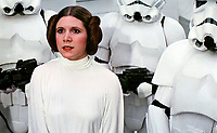 BNPS.co.uk (01202 558833)<br /> Pic: PropStore/BNPS.<br /> <br /> A captured Princess Leia with Syd Wragg (l) wearing the actual helmet.<br /> <br /> A Stormtrooper helmet from the first Star Wars film has sold for almost £200,000 by a relative of a British country squire.<br /> <br /> Captain Robert Hawkins and his wife Anne were gifted the iconic helmet for staging the Star Wars Cross Country Team Event at their English manor house in 1978.<br /> <br /> The bizarre equestrian event was attended by Carrie Fisher, who played Princess Leia, Darth Vader actor David Prowse, Peter Mayhew, who played Chewbacca, and football pundit Jimmy Hill.