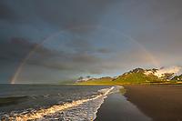 Rainbow over the Aleutian mountain range and the sandy beach shore of Katmai National Park, Alaska Peninsula, southwest Alaska.