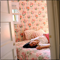 Woman laying on bed in floral wallpapered bedroom<br />