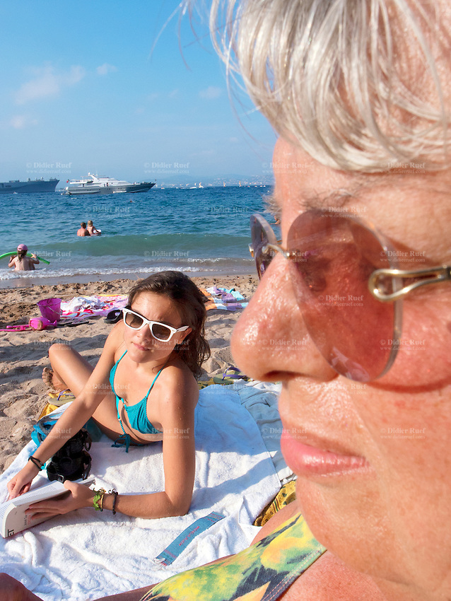 France. Alpes-Maritimes department. Théoule. The grandmother Claude Ruef and her granddaughter Micaela Ruef on the beach in the summer. Sunbathing, reading book, holiday and farniente. Mediterranean sea. 16.08.12 Model released. © 2012 Didier Ruef