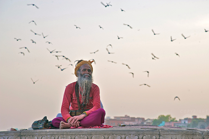 A Sadu on the bank of the Gabges Varanasi India,with birds flying over head.