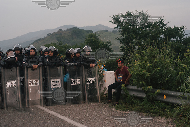 A local rests by the side of a road, unable to cross a bridge due to a police blockade on the outskirts of Arriaga.