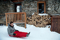 A boy sledding on snow-covered village streets in Bonneval sur Arc, Savoie, France, 16 February 2012.