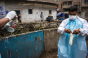 Laboratory assistants from the Institute of Serology prepare to collect the sewage samples from a sewage in Shyam Lal lane in Kolkata to monitor the polio virus in urban Bengal.