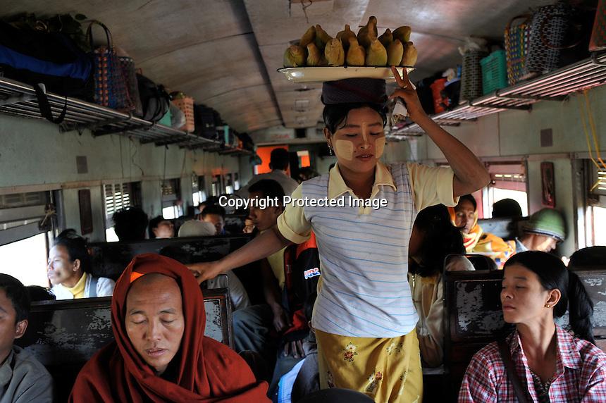 A vendor sells corn on the Mandalay to Rangoon train , Burma Nov 2008.  <br /><br />Photo by Richard Jones