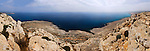 Panoramic view of the Mediterranean Sea, Cape Gkreko, Cyprus. With a young woman sitting alone on the rocks. Image © MaximImages, License at https://www.maximimages.com