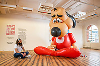 BNPS.co.uk (01202 558833)<br /> Pic: MaxWillcock/BNPS<br /> <br /> Pictured: GIANT gallery attendant Thomas Beauchamp sat beside 'Underdog', a giant, inflatable cartoon dog in a superhero costume created by American artist Chad Person this year, at the GIANT gallery in Bournemouth.<br /> <br /> 'Big Medicine', an exhibition celebrating our connection with one another in public space, is the inaugural display in GIANT, a new 15,000 square foot gallery in a former Debenhams in Bournemouth.