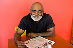 Mature African American man sitting at cafe table, smiling, portrait