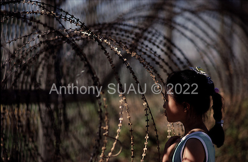 Korean DMZ<br /> P'am Mun Jeon<br /> July 3, 1988<br /> <br /> A young South Korean girl looks through the fence into North Korea at the 38th parallel DMZ which separates the two countries.