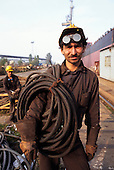 Gdansk, Poland. Shipyard worker wearing hard hat and protective goggles carrying a welding cable.