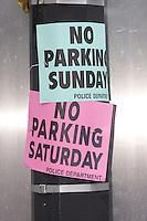 """Signs on a utility pole advising of """"No Parking"""" and Saturday and Sunday due the 9/11 Memorial Ceremony."""