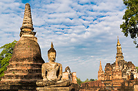 Wat Maha That temple, Buddha statues with beautiful golden hour morning light, under a cloudy sky, in the famous Sukhothai Historical Park, Thailand