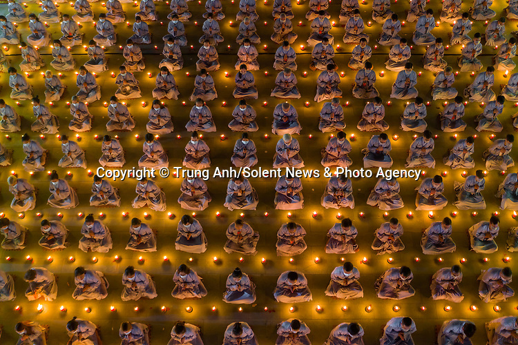 """Pictured:  Thousands of people take part in the Buddha Amitabha's memorial ceremony held at the Hoang Phap Pagoda in Ho Chi Minh City, Vietnam. <br /> <br /> Participants in the annual event, surrounded by candles, wore Buddhist robes and face masks in accordance with Covid-19 regulations.<br /> <br /> Photographer Trung Anh said, """"the global pandemic is currently under control in Vietnam, enabling this event to go ahead safely.""""<br /> <br /> <br /> Please byline: Trung Anh/Solent News<br /> <br /> © Trung Anh/Solent News & Photo Agency<br /> UK +44 (0) 2380 458800"""
