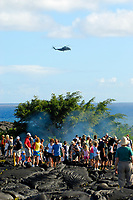 military helicopter flys by visitors on the Hawaii, USA county public viewing trail, as an active lava flow starts to cover the trail and burn through the trees, near a large lava flow from Royal Gardens subdivision flowing into the ocean, Waikupanaha ocean entry, Kilauea volcano, east of Hawaii, USA Volcanoes National Park, Big Island of Hawaii, USA