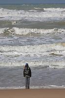 Kind, Mädchen steht am Strand und schaut auf das Meer, Ozean, Brandung, Dünung, Wellen, Mittelmeer