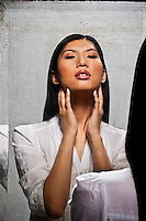 Reflection of young Asian woman in antique mirror touching her neck