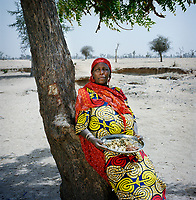 Ramata Modou, 58, holds a meal of ground red maize, white rice and crushed mango leaves. This will be the only food she and her six children will eat today. It was gathered by begging from house to house in a village near the IDP camp where they live and where Ramata is the appointed leader. <br />  <br /> During an attack on her village, on the border with Nigeria, Ramata Modou's husband suffered a heart attack and her 17 year old daughter and grandchild were taken. Following the attack Ramata and her children, aged from five to 16 years old, fled their village, eventually arriving in Meme, where, for the first two months, they all slept under trees. <br /> <br /> Ramata says: 'When the fighters came into the village, my husband started shaking and trembling. He was holding his head. When they arrived, one man was standing at the door with a gun. Another one put his leg on my mattress and the other one was pulling my daughter. My daughter was screaming and I was screaming, but they didn't hit me. Leaving my village was very difficult. We used to own cattle and sheep, but we had to leave all of those things behind. We had no choice, we had to leave. Even the roofs of some of the houses have now been stolen.'