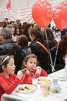 """Switzerland. Canton Ticino. Bellinzona. Two young girls  eats food during Easter sunday at Officine FFS. Stabilimento Industriale SBB CFF FFS Cargo. Railway workers on strike. Building's occupation. Red balloons: """" Giù le mani dall'Officina di Bellinzona"""". © 2008 Didier Ruef"""