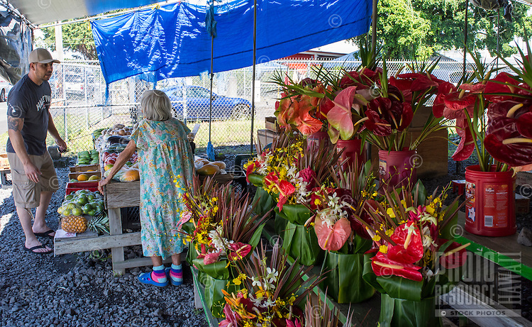 A silver-haired flower and produce vendor talks with a customer at the Hilo Farmers Market in Hilo, Big Island of Hawai'i.