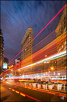 Flatiron Building with colorful traffic light trails, as if they were light painting strokes across the space.