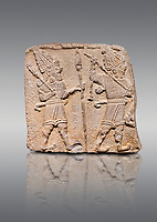 Aslantepe Hittite relief sculpted orthostat stone panel. Limestone, Aslantepe, Malatya, 1200-700 B.C. Anatolian Civilisations Museum, Ankara, Turkey. Scene of two Gods walking one carrying a spear, dressed in tunics.<br /> <br /> Against a gray background.