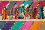 A group of Hindu pilgrims laden with luggage walk along the Ganges River, between colourful saris drying in the sun.