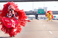 "Robert Stevenson, ""flag boy"" and the rest of the Golden Comanches Mardi Gras Indians parade on the interstate to the Superdome in New Orleans on February 28, 2006."