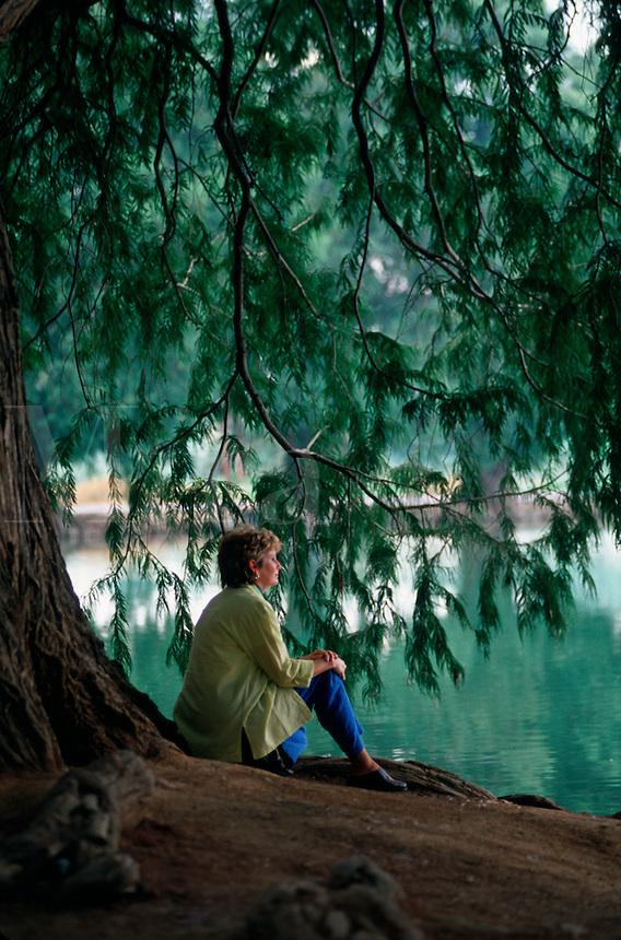 Women sits by edge of lake.