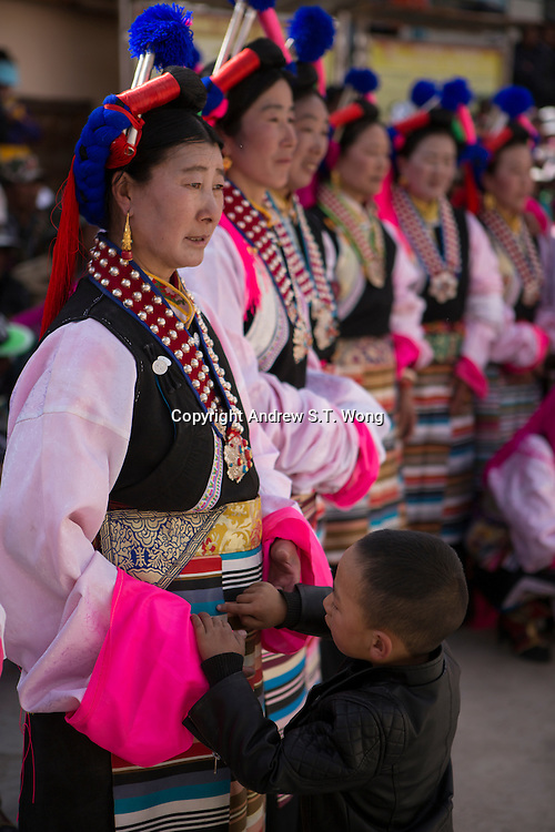 East Village, Diqing Tibetan Autonomous Prefecture, Yunnan Province, China - A Tibetan boy checks the traditional costumes of his mother after she performed  Xianzi Dance, February 2017.