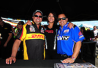 Jun. 2, 2012; Englishtown, NJ, USA: NHRA top fuel dragster driver Brandon Bernstein (right) and Funny car driver Jeff Arend (left) pose with Toyota girl during qualifying for the Supernationals at Raceway Park. Mandatory Credit: Mark J. Rebilas-