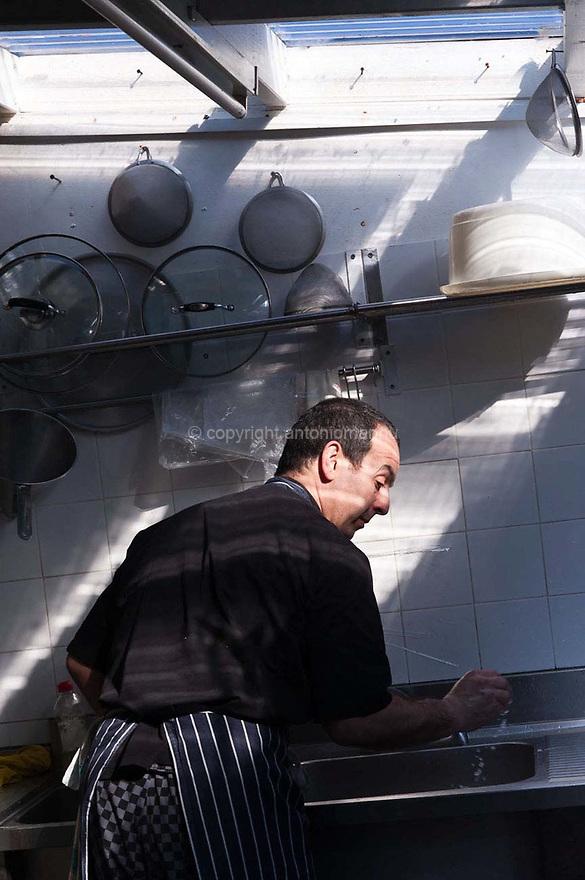 """Chenàbura 5 de martzu de su 2010 Londra (Regnu Unidu) <br /> Antonello Serra, nàschidu in Aristanis in su 1961, si nch'est tramudadu a Londra in su 1995 pro traballare coghineri e pro l'assegurare curas adeguadas a sa fìgia Giorgia. In su 2006, paris a su connadu Roberto Brai, at abertu, in su cuarteri de Brockley in Londra, su ristorante """"Le Querce"""". Inoghe est fotografadu traballende in coghina.<br />  <br /> Venerdì 5 marzo 2010 Londra (Regno Unito) <br /> Antonello Serra, nato ad Oristano nel 1961, si trasferisce a Londra nel 1995 per lavorare come cuoco e per garantire cure adeguate a sua figlia Giorgia. Nel 2006, insieme al cognato Roberto Brai, apre, nel quartiere di Brockley a Londra, il ristorante """"Le Querce"""". Qui è ritratto mentre lavora in cucina. <br /> <br /> Friday 5th March 2010 London (United Kingdom) <br /> Antonello Serra, born in Oristano in 1961, moves to London in 1995 to work as a chef and to ensu- re adequate healthcare for his daughter Giorgia. In 2006, together with his brother in law Roberto Brai, he opens, in the neighbourhood of Brockley in London, the restaurant """"Le Querce"""". Here he is portrayed while he works in the kitchen."""